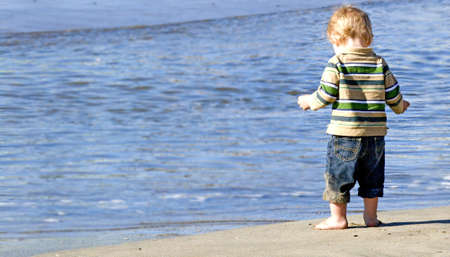 back of small boy at the edge of the ocean contemplating going in the water photo