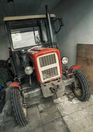 Old rusty tractor in a garage  photo
