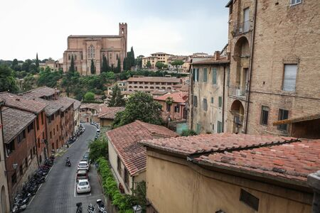 Siena, Italy – July 11, 2013 – View at the Via di Fontebranda street and surrounding old buildings in Siena, Italy with Gothic Basilica of San Domenico in the background  A few unrecognizable people visible in the picture   Stock Photo - 22493258