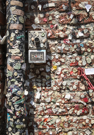 Verona, Italy – July 18, 2013 – Colorful bubble gums with remnants of love notes stuck to the ancient brick wall and adjoining gutter in the courtyard of Juliet s House tourist attraction in Verona, Italy   Stock Photo - 22493259