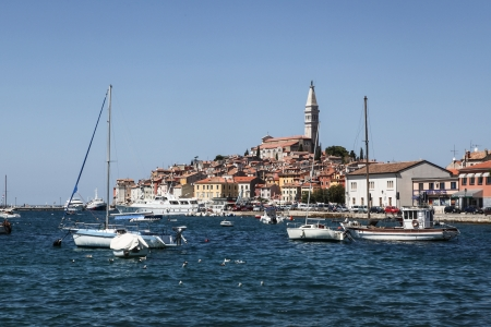 Rovinj, Croatia – August 8, 2012 - View at the historic part of Rovinj in Croatia, with the bell tower of St  Euphemia Basilica, town buildings and marina with sailboats  Stock Photo - 22716004