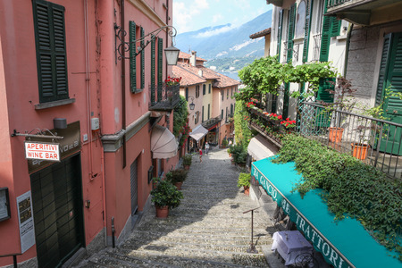 Bellagio, Italy - July 8, 2013  Street in Bellagio with shops and Lake Como in the background  Few people visible in the picture  Bellagio is a municipality in northern Italy, situated on Lake Como
