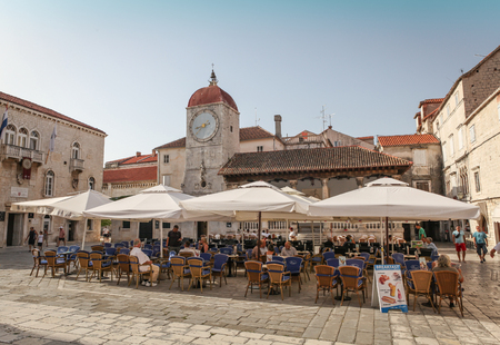 Trogir, Croatia - August 6, 2012  Main town square in historic center of Trogir with San Sebastian church clock tower and people sitting in a restaurant  Trogir is a historic town in Split-Dalmatia County in Croatia
