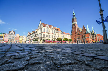 Wroclaw, Poland - September 6, 2008  Low angle view of the Market Square in Wroclaw, Poland with the Town Hall and other historic buildings  Pedestrians visible in the picture
