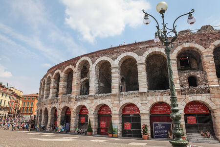 Verona, Italy - July 18, 2013  Verona Arena, famous Roman amphitheater on Piazza Bra in Verona, Italy, with groups of tourists and surrounding buildings