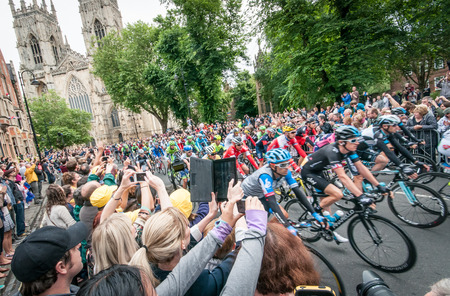 York, United Kingdom - July 6, 2014  People watch the Tour de France peleton riding past York Minster in York, UK  Tour De France is one of the most prestigious cycling contests in the world
