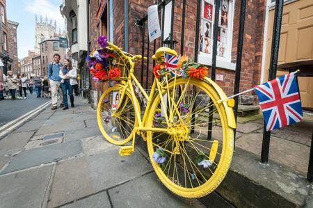 decorated bike: York, Regno Unito - 5 luglio 2014 La gente cammina davanti a una moto gialla decorata a York durante la gara ciclistica Tour de France 2014