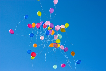 Balloons released into the clear blue sky after a wedding with closeup of a small group of balloons photo