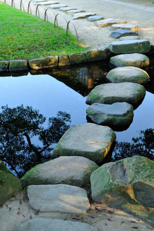 Stepping stones crossing water in the Korakuen Japanese garden in Okayama, Japan