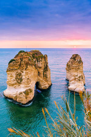 Beautiful sunset on Raouche, Pigeons Rock. In Beirut, Lebanon.Sun and Stones are reflected in water.dense clouds in the sky. Stock Photo