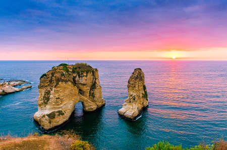 Beautiful sunset on Raouche, Pigeons Rock. In Beirut, Lebanon.Sun and Stones are reflected in water.dense clouds in the sky. Фото со стока