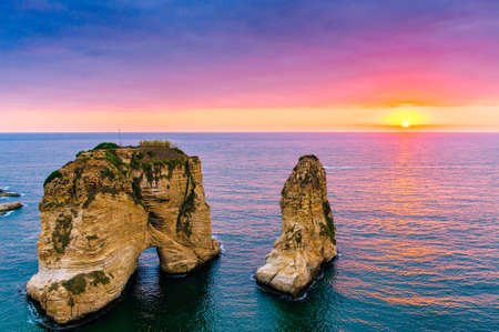 Beautiful sunset on Raouche, Pigeons Rock. In Beirut, Lebanon.Sun and Stones are reflected in water.dense clouds in the sky. Фото со стока - 87104133