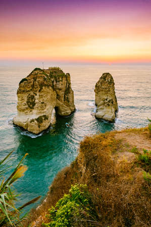 Beautiful sunset on Raouche, Pigeons Rock. In Beirut, Lebanon.Sun and Stones are reflected in water.dense clouds in the sky. Banque d'images