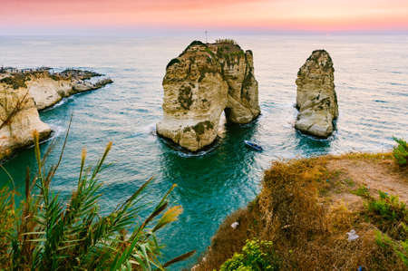 Beautiful sunset on Raouche, Pigeons Rock. In Beirut, Lebanon.Sun and Stones are reflected in water.dense clouds in the sky. 版權商用圖片