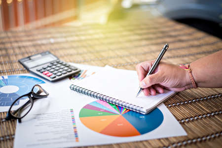Woman writing idea for Analysis Business and financial report.