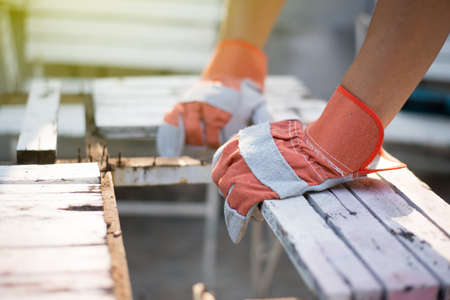 The carpenter is repairing the table. By wearing gloves to prevent injury. Stock Photo