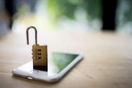 Padlock on blur phone over colorful lighting,phone data security concept. Stock Photo