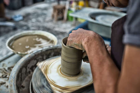 Mans hands. Potter at work. Creating dishes. Potters wheel. Dirty hands in the clay and the potters wheel with the product