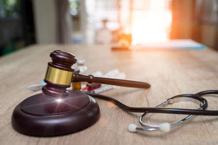 medical law and a judge gavel on desk in the library. concept of legal education. Stock Photo