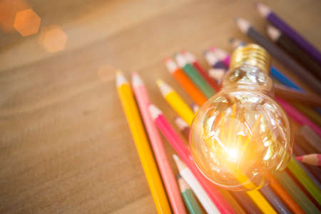 Concept idea of education Coloring pencils in glass jar Or return to school on a light cream background .