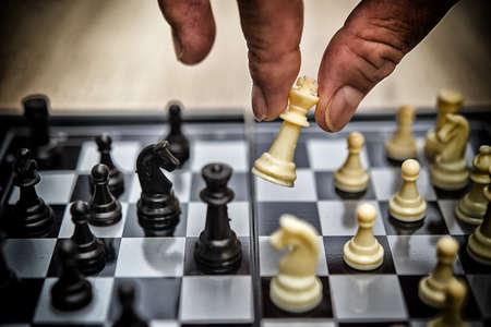 Hand of businessman playing chess,High dynamic range tone
