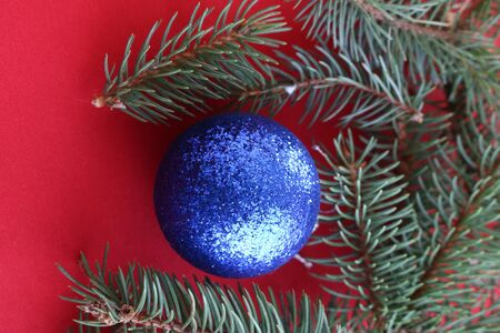 Christmas frame of fir branch and blue balls on a red background