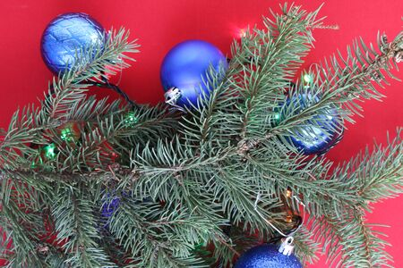 Christmas frame of fir branch and blue balls on a red background Фото со стока