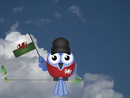 compatriot: Comical Welsh flag waving bird Patriot sat on a tree branch against a cloudy blue sky
