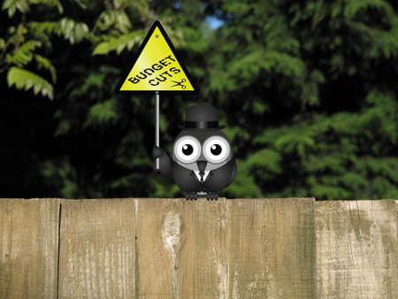 cutback: Comical bird warning against Government budget cuts perched on a timber garden fence against a foliage background Stock Photo