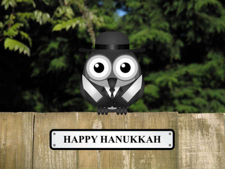 comical: Comical bird with happy Hanukkah message perched on a timber garden fence against a foliage background Stock Photo