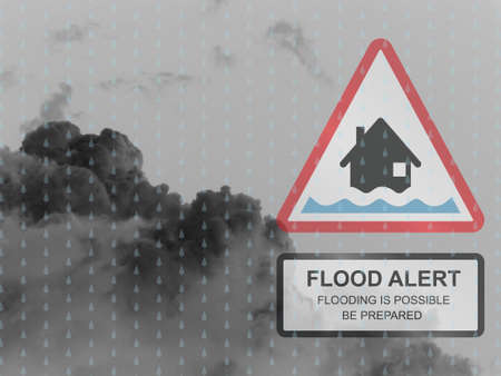 deluge: Amber flood warning sign against a dark raining cloudy skyscape
