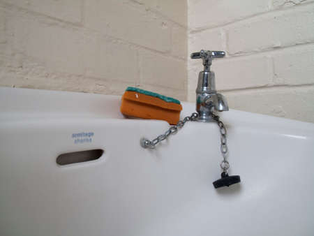 grimy: Unhygienic grimy wash hand basin tap with dirty cleaning scourer pad Editorial
