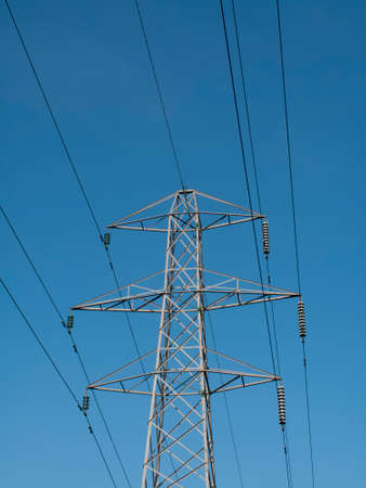 steel tower: Electricity supply pylon and cables set against a blue sky