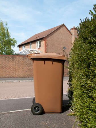wheeling: Andover, Hampshire, England - May 05, 2016: Brown recycling wheeling bin awaiting collection by local council