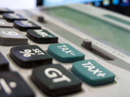 taxable income: A dusty old calculator with shallow depth of field with focus centred on the minus tax button