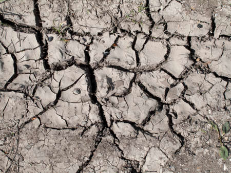Dry cracked soil in the countryside due to shortage of rainfall Stock Photo