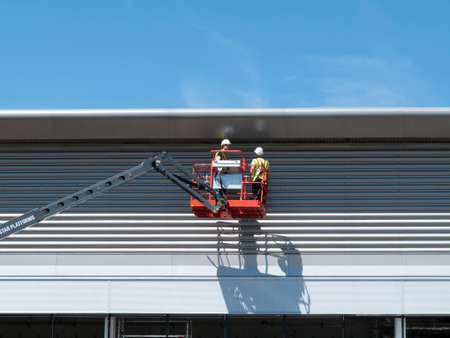 middlesex: construction workers on mobile access platform installing on cladding to new commercial warehouse development