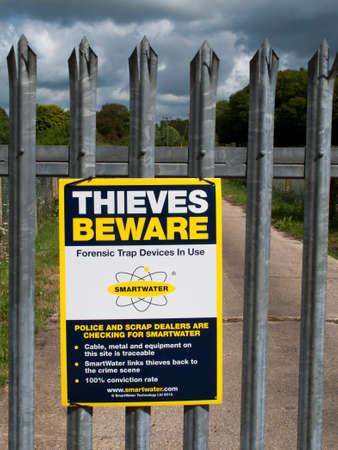 deter: Smartwater Thieves beware forensic trap device in use sign on gate to rural agricultural land Editorial