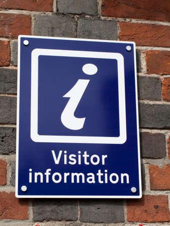 Bezoekersinformatiebord opgezet op bakstenen muur Redactioneel