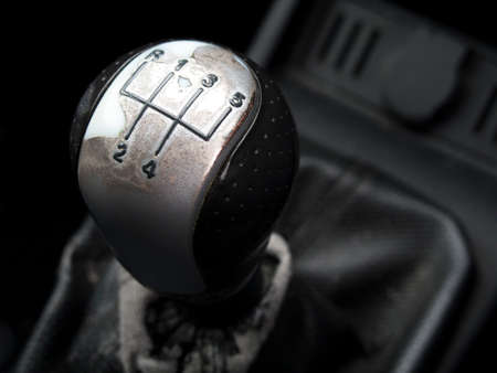Worn five speed manual car gearstick with shallow depth of field