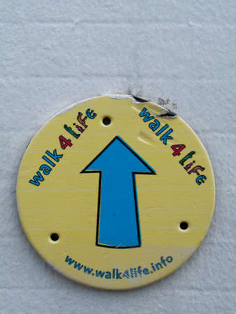 Walk for life badge mounted on brick wall, sponsored events to raise money for various charities Editorial