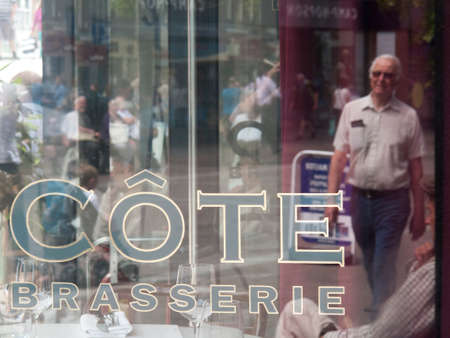 Cote Brasserie French restaurant name with street scene reflected in glass window