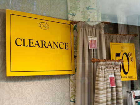 discounting: Sale clearance sign in drapery retail shop window