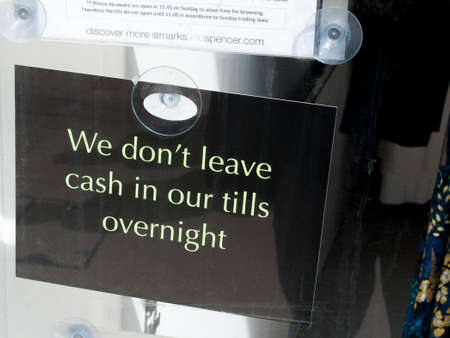 deterrence: We do not leave cash in our tills overnight sign in shop window aimed to deter thieves