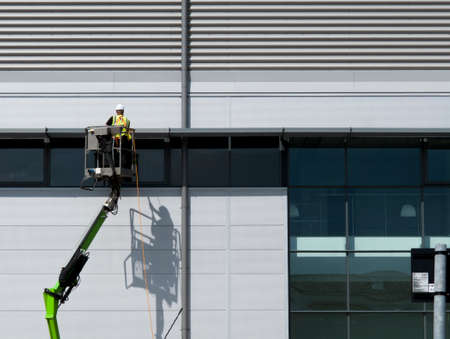 Construction worker on mobile boom lift cleaning external rainscreen cladding on new build office and warehouse development