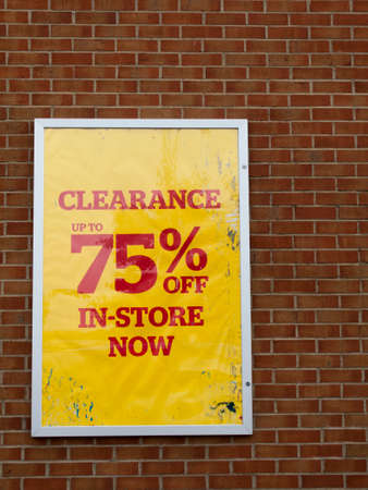 discounting: 75 percent off in store now retail store clearance sale sign mounted on brick wall Editorial