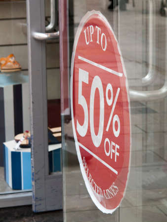 discounting: 50 percent sale sign in clothing shop window