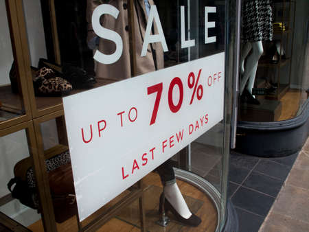 merchant: Seventy percent off last few days sale sign in clothing shop window