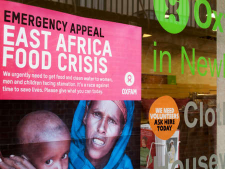 Manifesto di emergenza di Oxfam nella vetrina di un negozio di beneficenza, crisi alimentare in Africa orientale