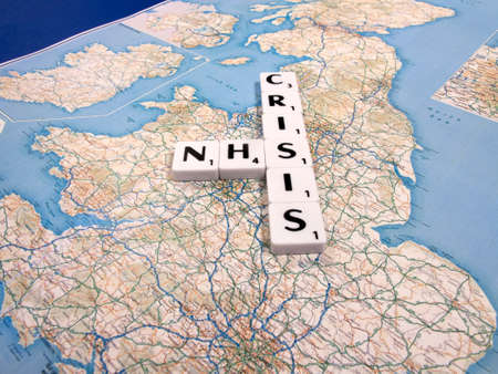 representation of the funding and staffing crisis effecting the National Health Service on United Kingdom map background Editorial